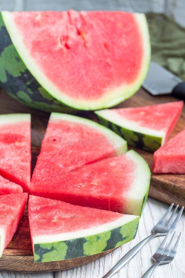 Scheiben der frischen samenlosen Wassermelone schnitten in Dreieckform auf der hölzernen Platte, vertikal stockbild
