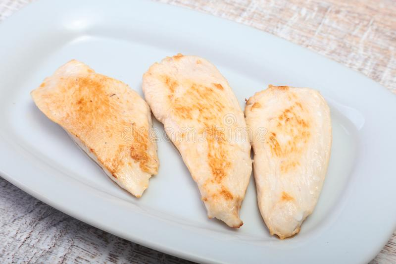 Scheiben der gebratenen Hühnerbrust und der Tomate auf weißer Platte lizenzfreies stockfoto
