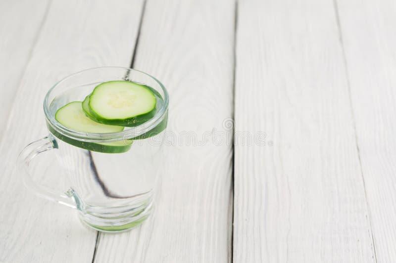 Scheiben der grünen frischen Gurke in der Glasschale mit Wasser auf alten hölzernen Planken stockfotografie