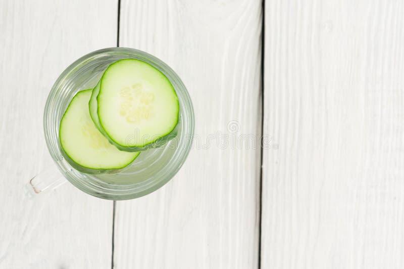 Scheiben der grünen frischen Gurke in der Glasschale mit Wasser auf alten hölzernen Planken lizenzfreie stockfotos