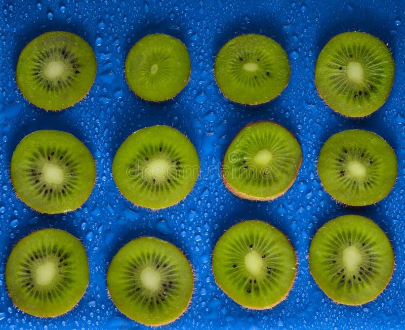 Scheiben der Kiwi im Wasser fällt auf einen blauen Hintergrund Fruchtkonzept stockfotos
