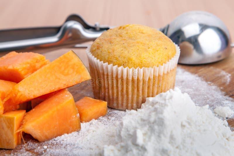 Scheiben der kleinen Kuchen, des Mehls und des Kürbises auf Küchentisch lizenzfreie stockbilder