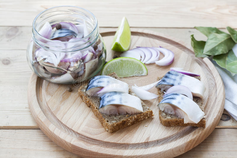 Scheiben der marinierten Makrele mit Zwiebel in einem Glas, in einem Kalk, in einem Lorbeer und in einem Brot auf hölzernem Brett stockfoto