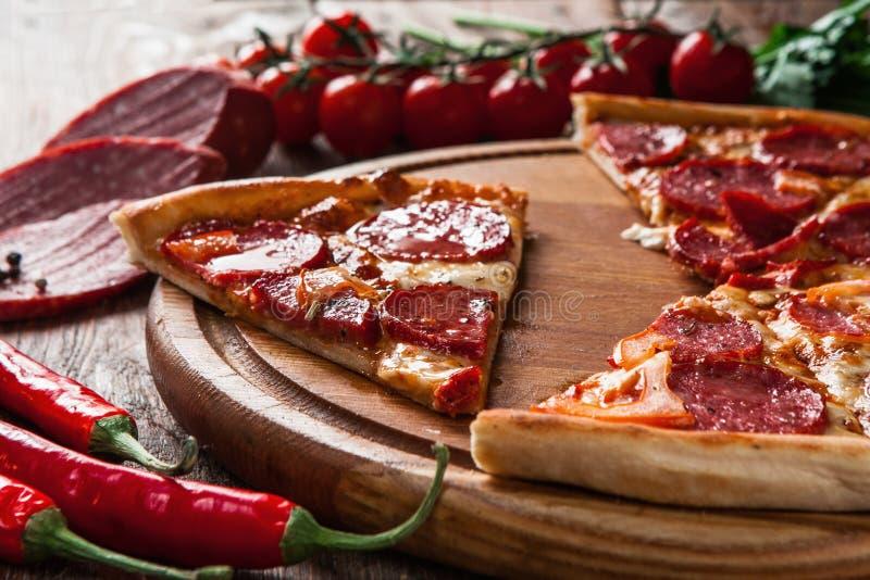 Scheiben der Pizza auf hölzerner Servierplatte Ungesunde Fertigkost, fett lizenzfreie stockfotografie