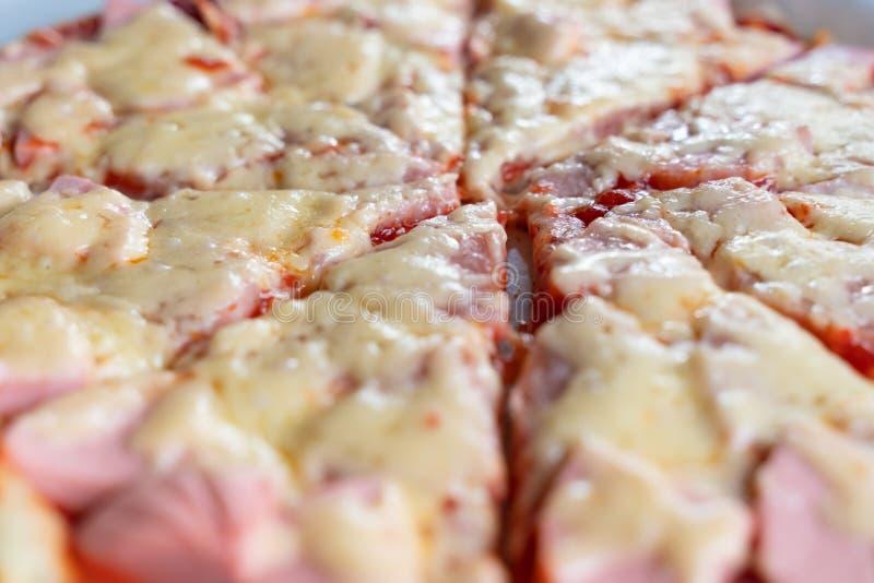 Scheiben der Pizza mit geschmolzener Käse- und Wurstnahaufnahme als Hintergrund stockfotografie