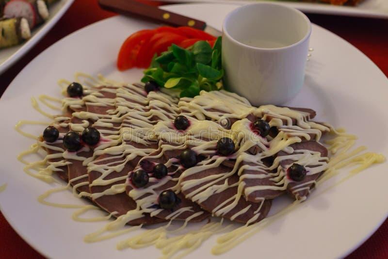 Scheiben der Rinderzunge auf einer Platte, verziert mit Mayonnaise und Oliven lizenzfreies stockfoto