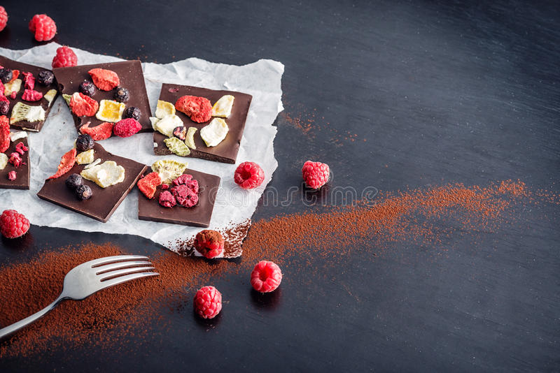 Scheiben der süßen Schokolade mit Früchten auf Weißbuch mit Frucht auf Platte, Süßspeise auf schwarzem Hintergrund Bild für Kondi stockfotos