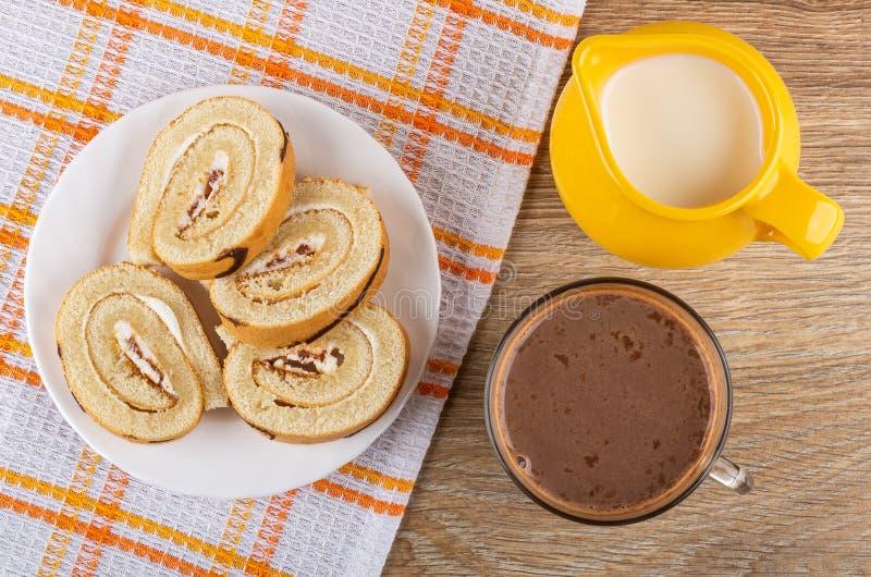 Scheiben der Schweizer Rolle in der Platte auf Serviette, Krug Milch, Kakao mit Milch in der Schale auf Tabelle Beschneidungspfad lizenzfreies stockbild