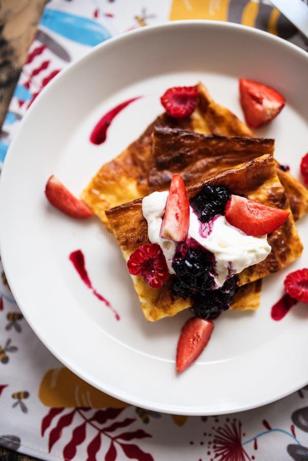 Scheiben des finnischen Pfannkuchens mit Sahne gedient und der Früchte lizenzfreie stockfotos