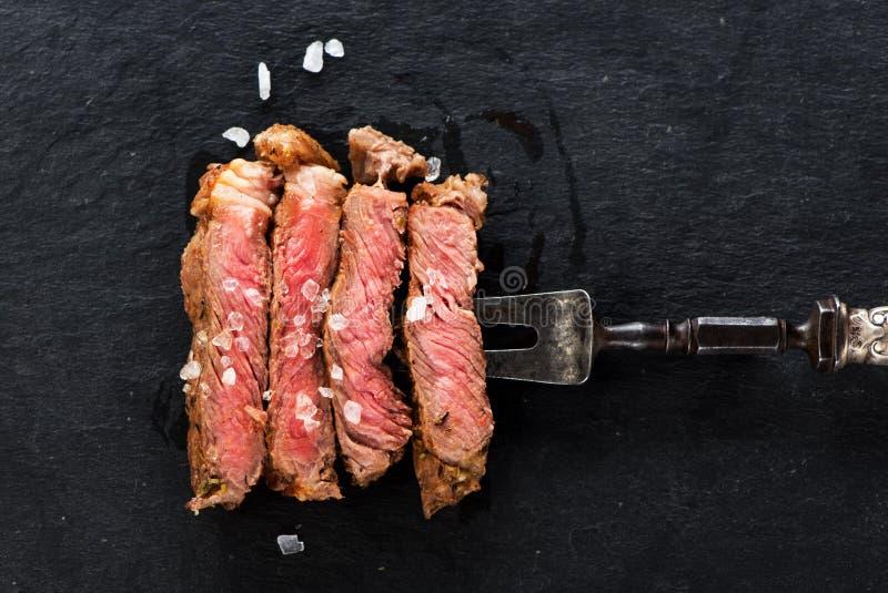 Scheiben des gegrillten Fleischgrillsteak Rippenauges auf Fleischgabel lizenzfreie stockfotografie