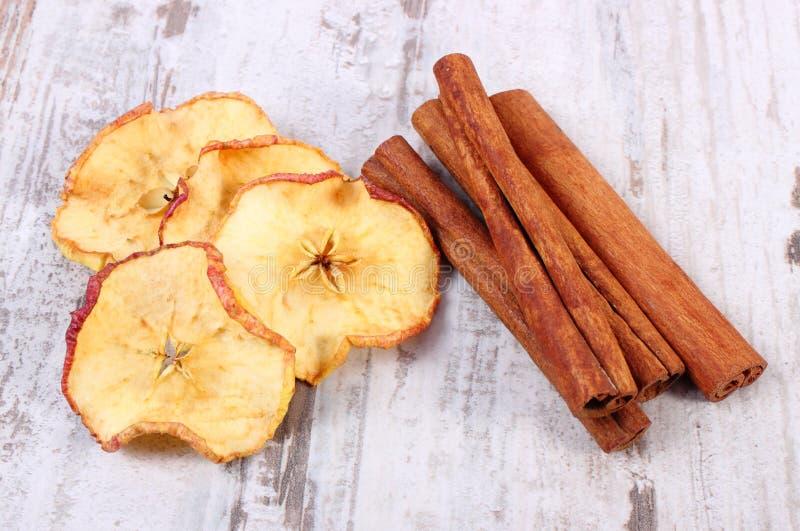 Scheiben des getrockneten Apfels und der Zimtstangen auf altem rustikalem hölzernem Hintergrund stockfotografie