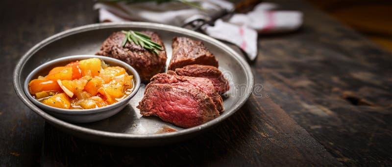 Scheiben des halb garen gebratenen Fleischsteaks und -Salsa sauce auf rustikalem hölzernem Hintergrund lizenzfreies stockfoto
