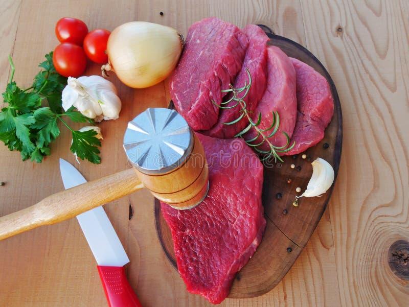 Scheiben des roten Fleisches angeboten mit einem Fleischstampfer lizenzfreie stockfotografie