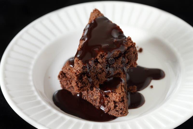 Scheiben eines Schokoladenkuchens auf weißer Platte mit Schokolade stockbilder