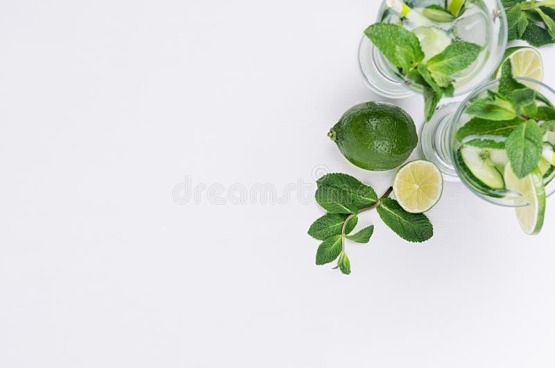 Scheiben kalken, Gurke, Blätter prägen, Eis und transparentes kaltes Getränk auf weißer hölzerner Planke, Draufsicht, Kopienraum stockbild