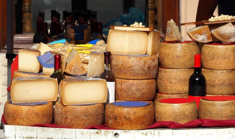 Scheiben und Räder von Pecorino-Käse zusammen mit Flaschen Cannonau, Weißwein, Teigwaren und anderen sardinischen typischen Telle lizenzfreies stockfoto