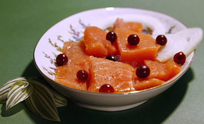 Scheiben von rohen Lachsen mit Moosbeeren und Zwiebel in der Schüssel lizenzfreie stockfotos