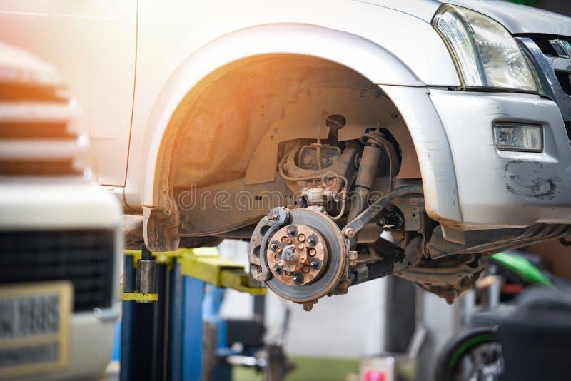 Scheibenbremse-Autoteil an der Garage - Kleinlastwagenbremsscheibe angehoben auf Aufzug, um Räder zu ändern oder zu reparieren stockfotos