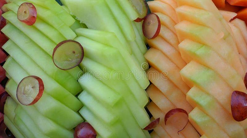 Scheibenhintergrund der tropischen Frucht Melone, Papaya und Traube essfertig lizenzfreie stockfotografie