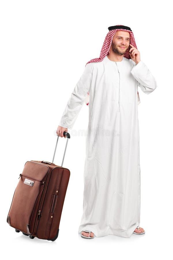 Scheich, der am Telefon spricht und ein Gepäck trägt stockfotografie