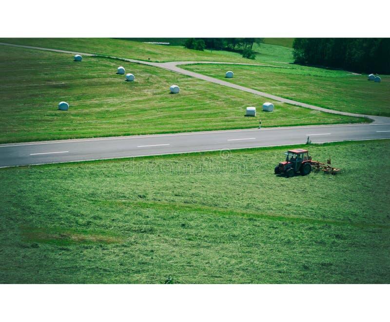 Scheidegg, Duitsland - Juni 06, 2019: De tractor draait droog gras op het gebied in een de zomerdag Broodjes van ingepakt, vers d stock foto