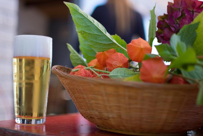 Scheidel, Люксембург - 8-ое сентября 2018: Свежее стекло пива рядом с корзиной с плодом физалиса стоковая фотография rf