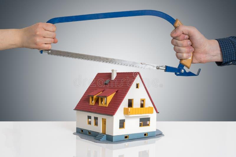 Scheiding en het verdelen van een huisconcept De man en de vrouw verdelen model van huis met zaag stock foto's