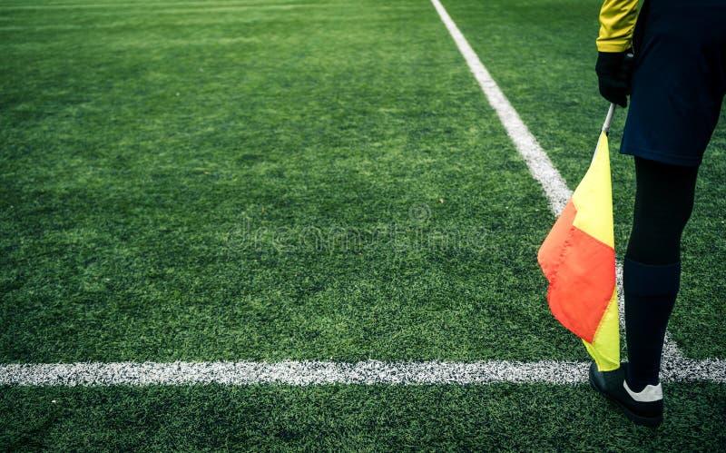 Scheidsrechtersvoetbal De scheidsrechter is op het gebied met vlag in de hand stock foto's