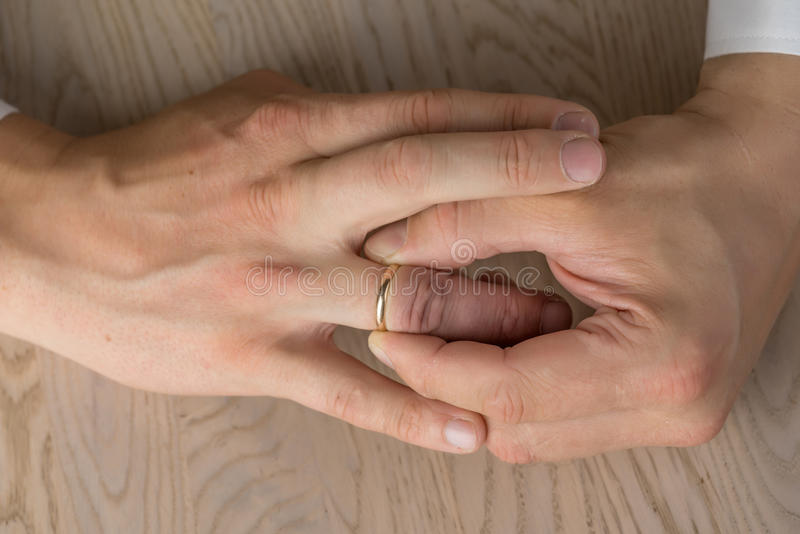 Scheidung, Trennung: Hände des Mannes Hochzeit oder Verlobungsring entfernend stockfotos