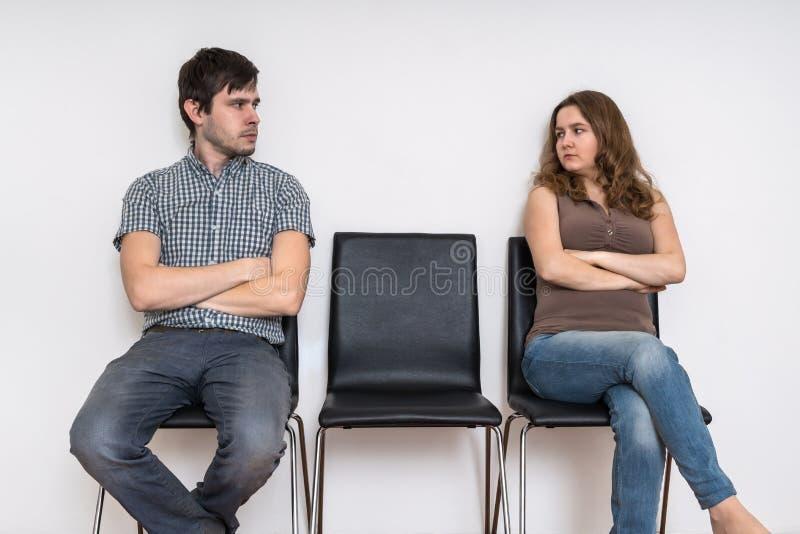 Scheidungs- und Verhältnis-Schwierigkeitskonzept Mann und Frau, die auf Stühlen sitzen und einander betrachten stockbild