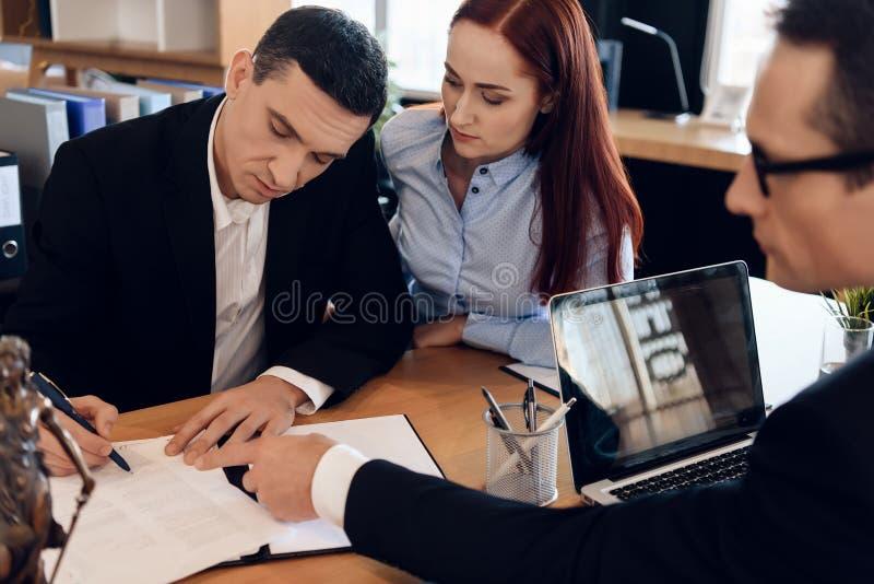 Scheidungsrechtsanwalt zeigt Mann, wo man Heiratauflösungsvereinbarung unterzeichnet stockfotografie