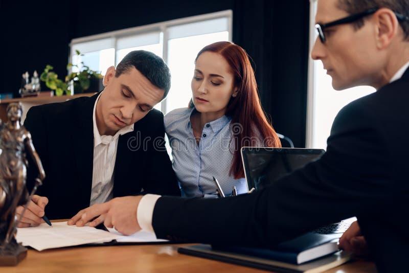Scheidungsrechtsanwalt zeigt Mann, wo man Heiratauflösungsvereinbarung unterzeichnet stockbild