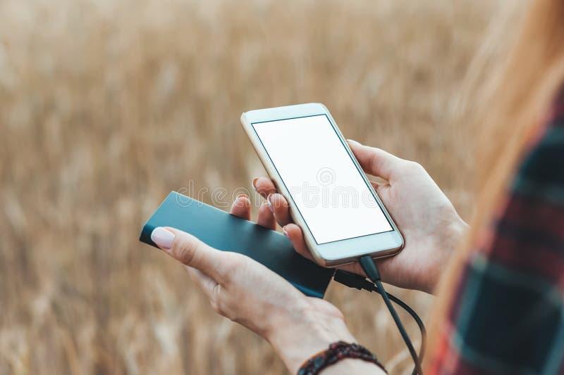 Schein oben vom Telefon und von der Bank in der Hand eines Mädchens, vor dem hintergrund eines gelben Feldes lizenzfreie stockfotos
