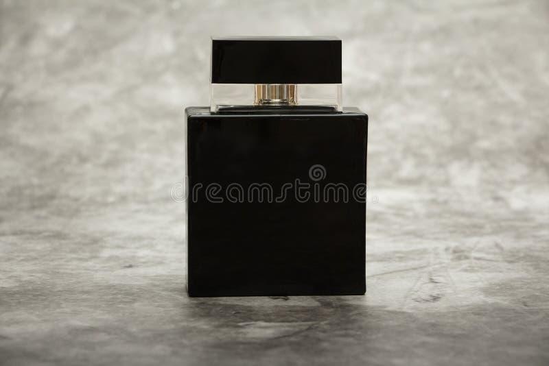 Schein oben von einer schwarzen Flasche Parfüm der Männer auf einem grauen Wandhintergrund des Ziegelsteines Platz für Text lizenzfreie stockfotos