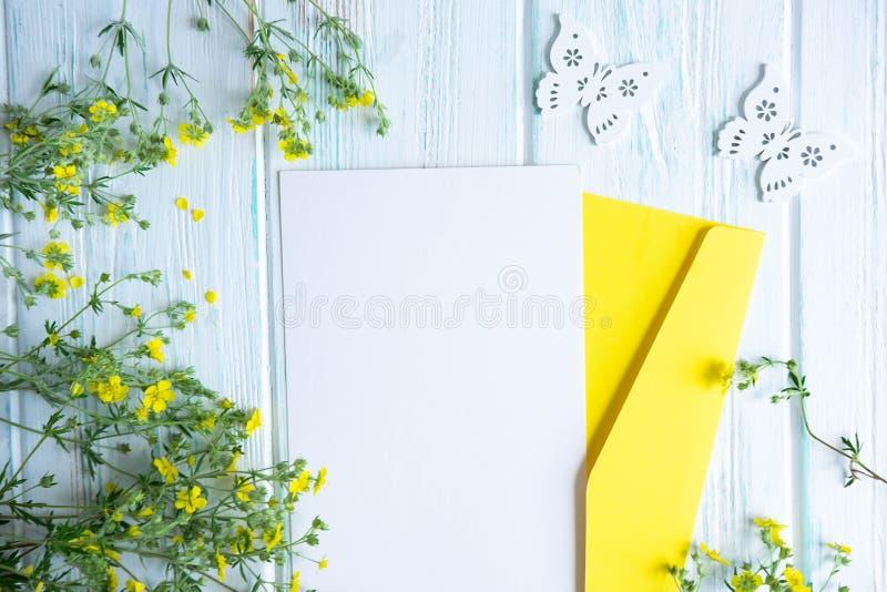 Scheinbare hohe Schablone mit Umschlag, Postkarte und kleinen gelben Wildflowers Feld für Glückwunschfarben mit Wildflowers Flach stockfotos