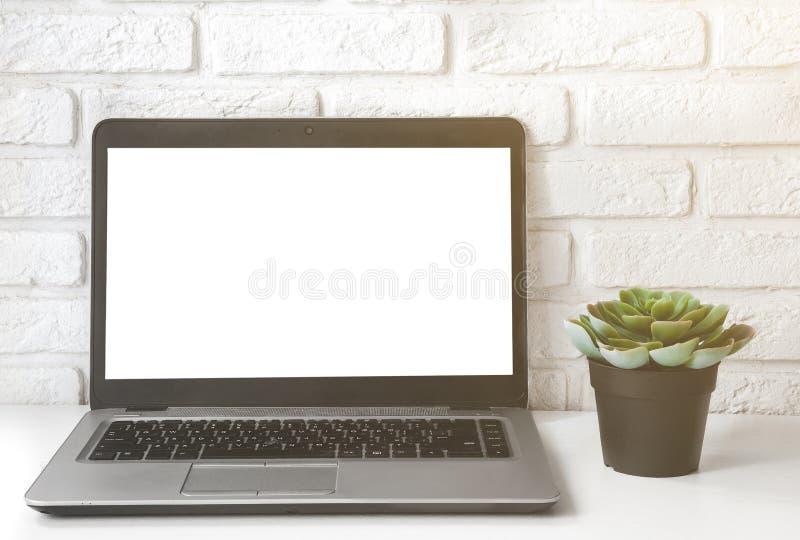 Scheinbarer hoher Laptop-Computer weißer leerer Bildschirm auf Vorderansicht der Arbeitstabelle saftige Anlage und weiße Backstei stockfoto