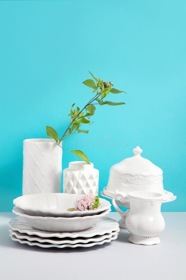 Scheinbares hohes Bild mit wei?er Tonware, Teller, Ger?ten und Blumenvasen auf grauer Tabelle gegen blauen Hintergrund mit Raum f stockfoto