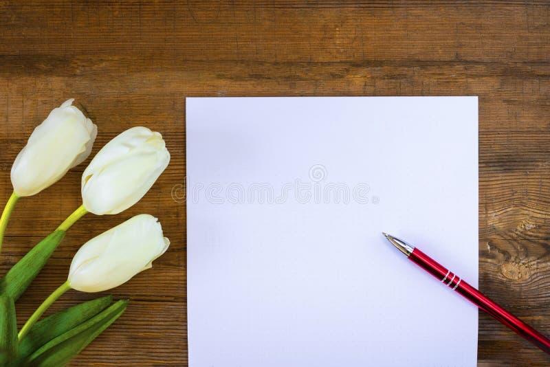 Scheinbares hohes leeres Blatt des Papiers mit rotem Stift und drei weißer Tulpen auf altem hölzernem rustikalem Hintergrund Glüc stockfotografie