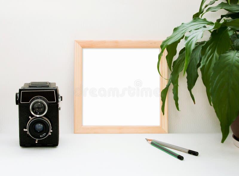 Scheinoben Holzrahmen, alte Kamera, Anlage und Bleistifte Innenquadratisches Plakathauptmodell mit hölzernem Rahmen und grüne B lizenzfreie stockfotografie