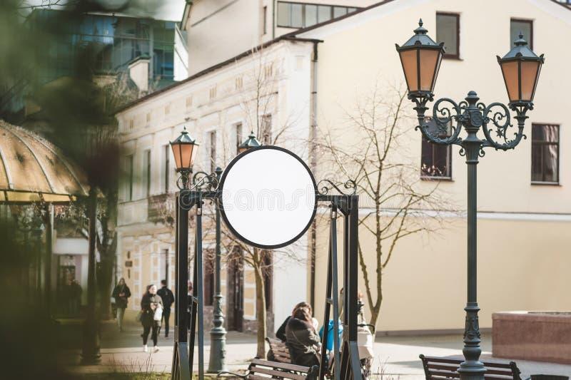 Scheinoben runde Anschlagtafel auf dem Hintergrund der Straße mit Leuten stockbild
