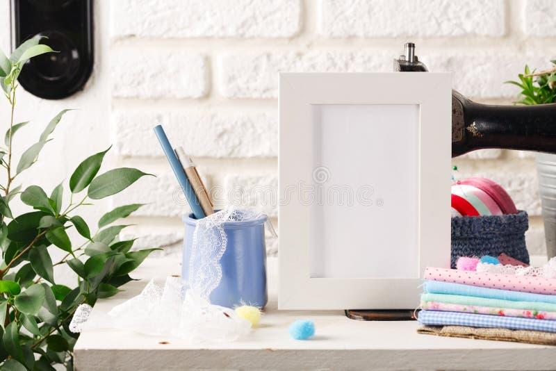 Scheinoben weißer Rahmen auf dem weißen Backsteinmauerhintergrund, den Nähmaschinen der Weinlese und den Stapeln von Geweben Mode stockbilder