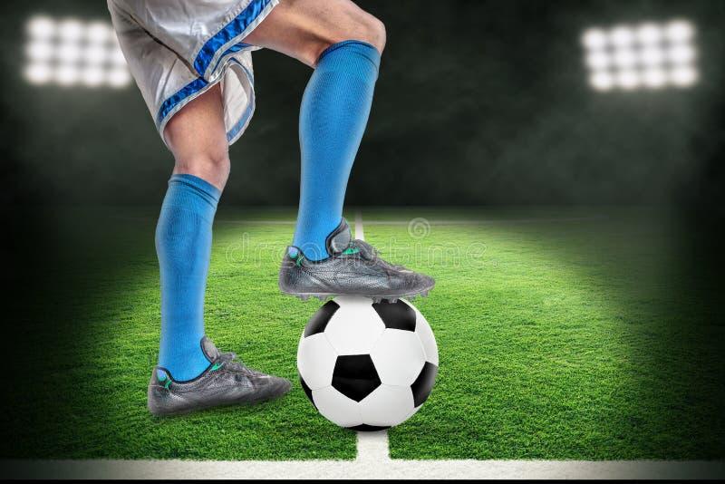 Scheinwerfer auf dem Fu?ball-Spieler, der ?ber Fu?ball Stadion im im Freien mit Kopien-Raum steht lizenzfreie abbildung