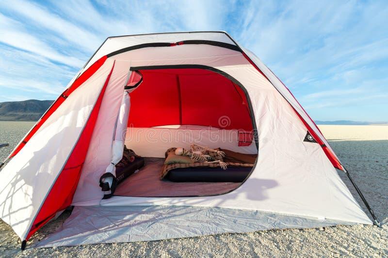 Scheletro che si rilassa in una tenda mentre accampandosi sul playa fotografie stock