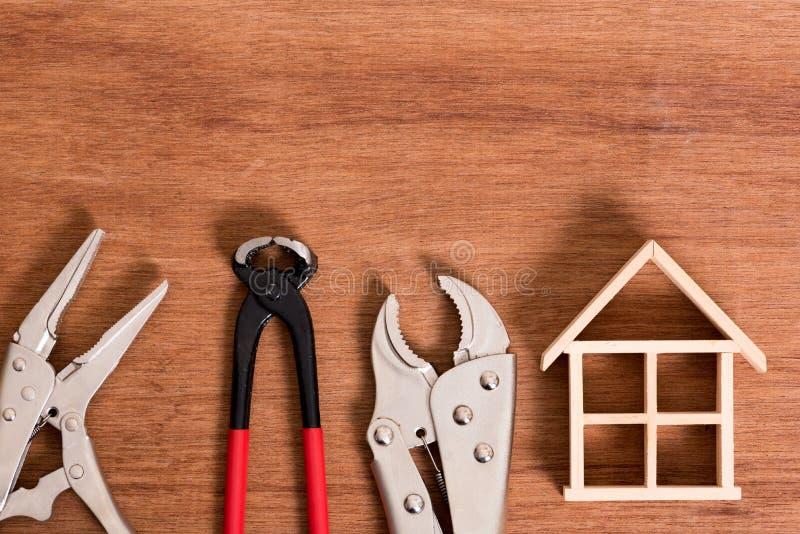 Scheletro della casa di legno con lo strumento per il problema della correzione su fondo di legno fotografie stock libere da diritti
