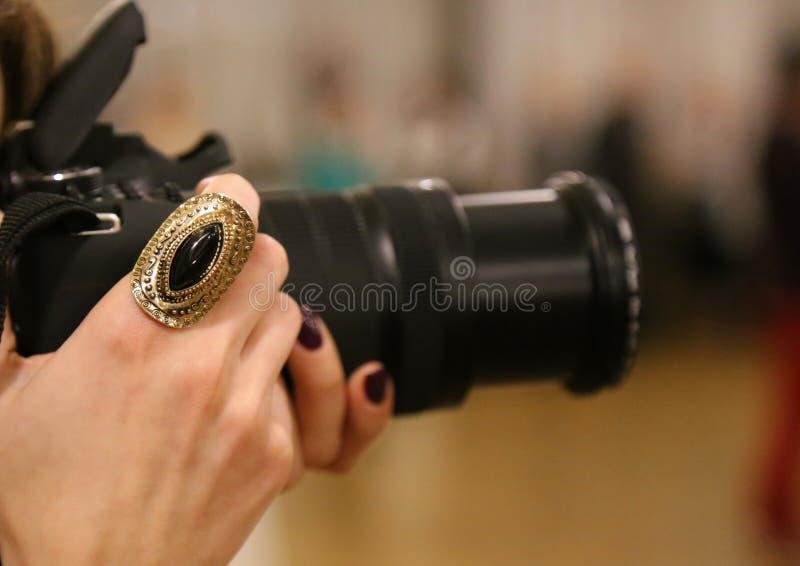Schellen Sie auf der Hand eines weiblichen Fotografen lizenzfreie stockfotografie