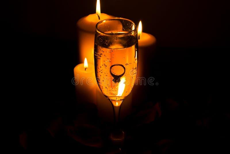 Schellen Sie in einem Champagnerglas und in den Kerzeleuchten lizenzfreie stockbilder