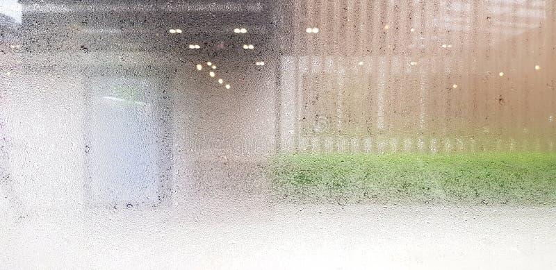 Schema artistico di vapore, vapore o goccioline d'acqua su vetro o specchio con fondo di struttura verde sfocato, luce ed esterno fotografie stock libere da diritti