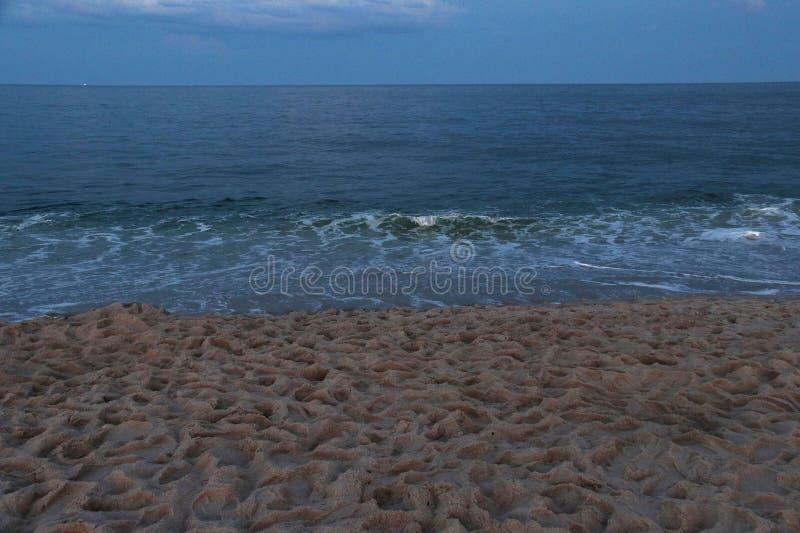 Schemering bij de oceaan met zandig strand met voetafdrukken royalty-vrije stock afbeelding