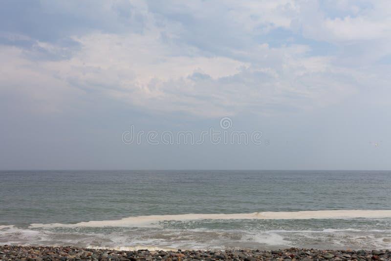 Schemering in het mooie beeld van de aardhorizon met blauwe hemel Oceaangolven op het strand met blauwe hemel met wolken op de ho stock fotografie