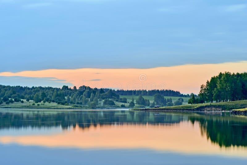 Schemering met bezinning van de avondhemel in water van het meer door een grote wolk wordt aangehaald die Achtergrond royalty-vrije stock afbeelding